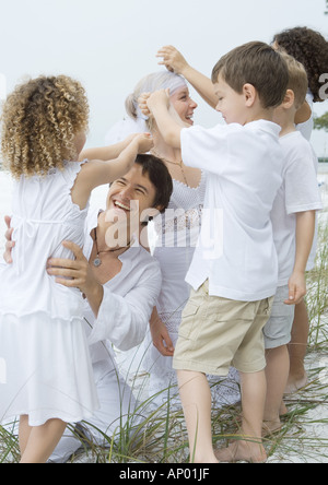 Bride and groom with children on beach - Stock Photo