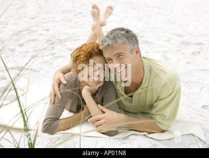 Mature couple lying on sand together - Stock Photo