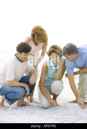Two mature couples crouching on beach - Stock Photo