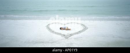 Child lying inside heart drawn on beach - Stock Photo