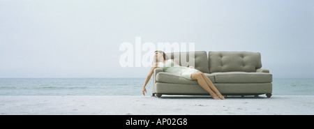 Woman reclining on sofa, on beach - Stock Photo