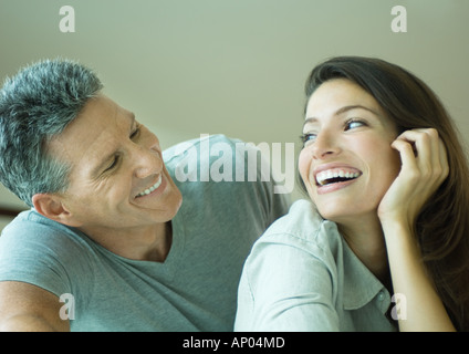 Couple smiling at each other, head and shoulders - Stock Photo