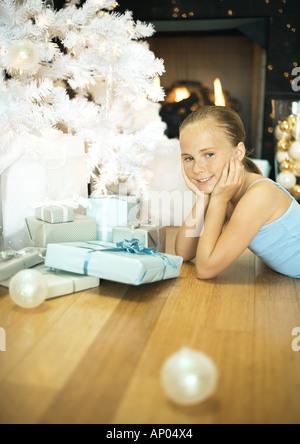 Girl lying on floor next to christmas tree - Stock Photo