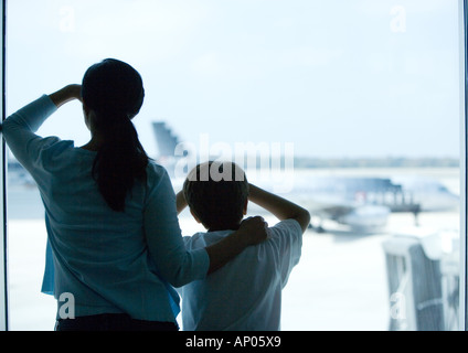 Woman and boy looking through window in airport - Stock Photo