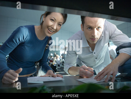 Woman and man filling out forms, looking at camera - Stock Photo