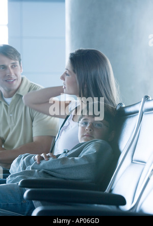 Family sitting in airport lounge, boy looking at camera - Stock Photo