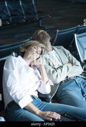 Travelers sleeping in airport lounge - Stock Photo