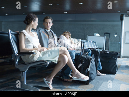 Travelers sitting in airport lounge - Stock Photo