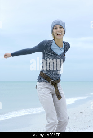 Young woman standing on beach, laughing, arms out - Stock Photo