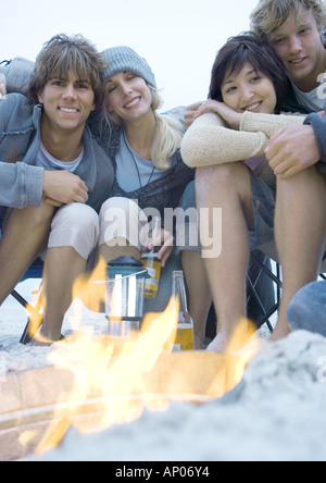 Young adult friends sitting around campfire - Stock Photo