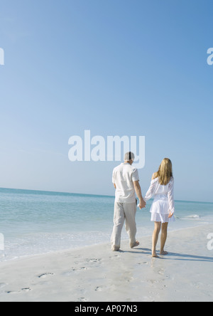 Couple walking on beach, rear view - Stock Photo