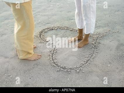 Woman standing inside heart drawn on beach, facing man, low section - Stock Photo