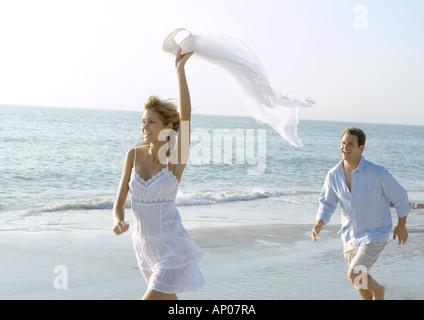 Couple running on beach - Stock Photo