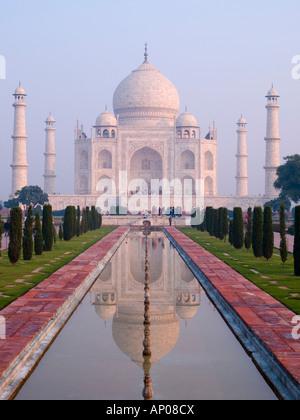 17th century Taj Mahal mausoleum in early morning light with reflection in water pool. Agra Uttar Pradesh India - Stock Photo
