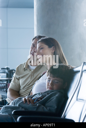 Family sitting in airport lounge, boy sleeping - Stock Photo