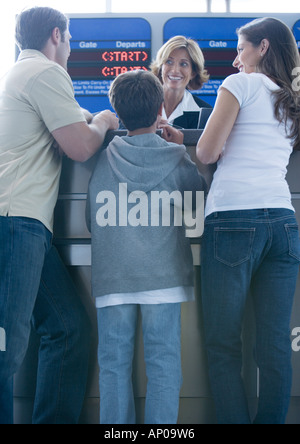 Family standing at airline check-in counter - Stock Photo