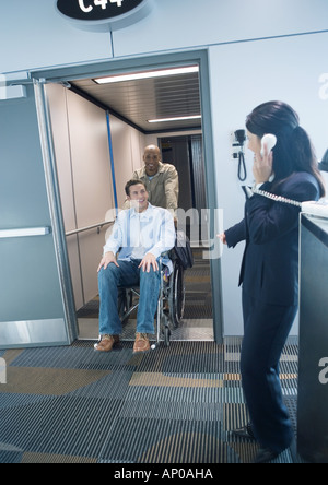 Traveler in wheelchair arriving at gate in airport - Stock Photo
