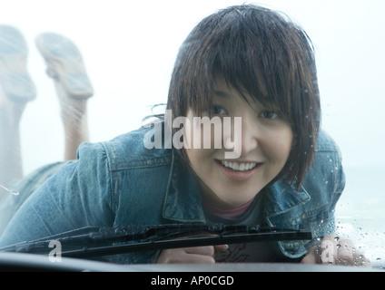 Woman lying on hood of car, looking through windshield - Stock Photo