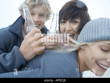 Three friends with beer bottles, smiling and laughing - Stock Photo
