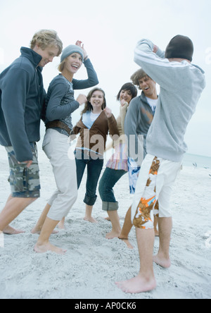 Group of young adult friends dancing on beach - Stock Photo