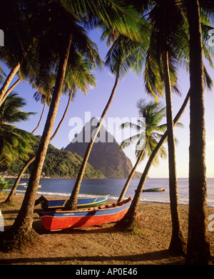 The Pitons tower above Soufriere beach on the Caribbean island of St Lucia as fishing boats lay on the beach below - Stock Photo