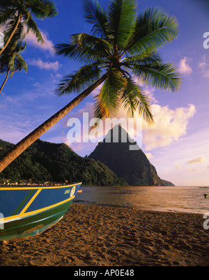 Late afternoon light on Soufriere Beach with the Petite Piton in the background Fishing boat rests on the beach - Stock Photo
