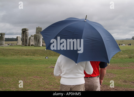 couple standing in the rain at stonehenge, wiltshire, england - Stock Photo