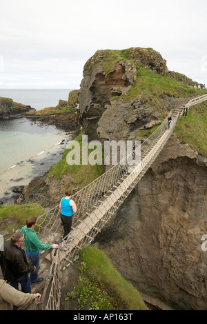 People crossing the Carrick a Rede rop bridge Co Antrim Northern Ireland - Stock Photo