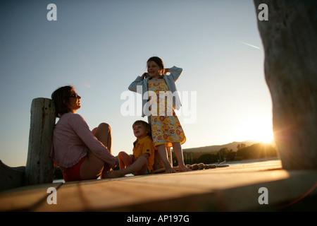 Family sitting on jetty, Santa Giulia Beach, Southern  Corse, France - Stock Photo