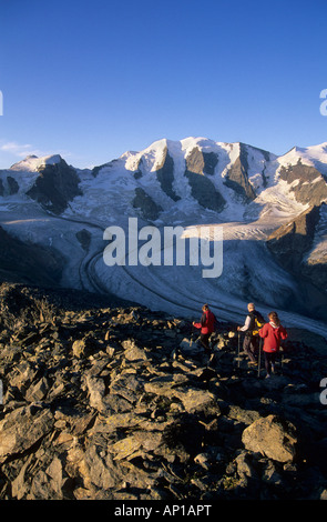 Three mountaineerers descending from summit of Munt Pers with view to Piz Palue and glacier of Pers, Pontresina, - Stock Photo