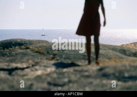 Woman standing on granite rock looking out on sea, Smoegen, Bohuslan, Sweden - Stock Photo
