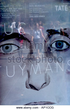 Summery young women are reflected in a Luc Tuymans Tate art gallery poster, on the sunny South Bank, London, UK - Stock Photo
