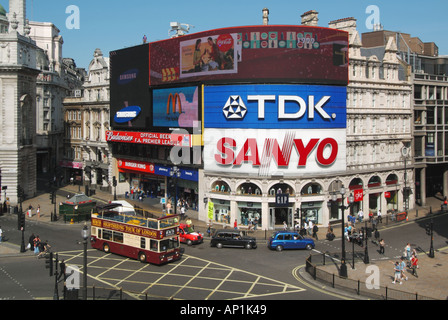 Looking down on open top tour bus & taxis crossing box junction at Piccadilly Circus with illuminated advertising - Stock Photo