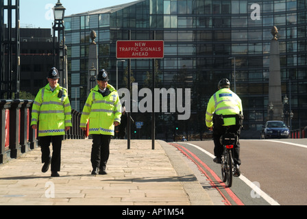 London Lambeth Bridge spanning River Thames 2 two police officers pounding beat on foot being passed by colleague - Stock Photo