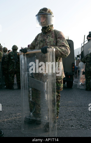 British Army soldier in riot gear stands guard on crumlin road at ardoyne shops belfast 12th July - Stock Photo