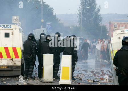 Police officers in riot gear face rioters on crumlin road at ardoyne shops belfast 12th July Stock Photo