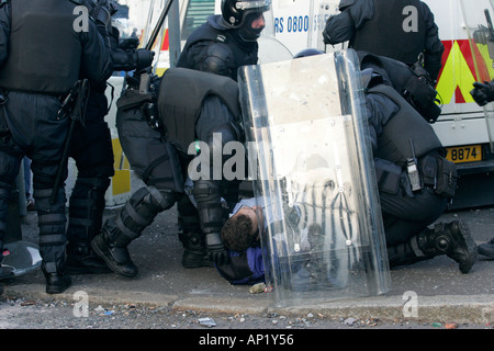 Police in riot gear attend to injured journalist hit by blast bomb during riot on crumlin road at ardoyne shops - Stock Photo