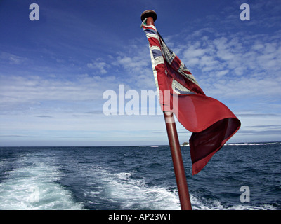 View over the stern of the boat on the way to Tresco, Isles of Scilly, UK, with a Union Jack flag flying from the - Stock Photo