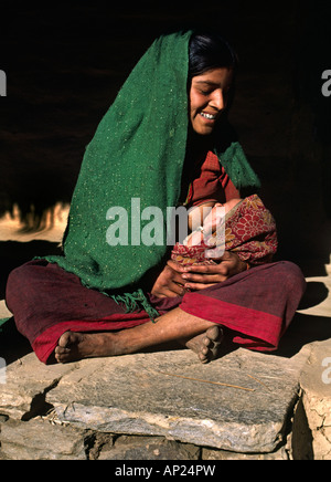 A NEPALI WOMAN of the CHETRI tribe NURSES her BABY ANNAPURNA REGION NEPAL - Stock Photo