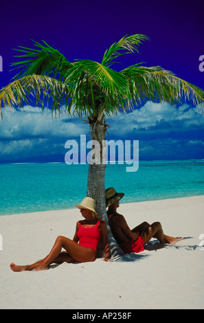 Couple on the beach under palm tree - Stock Photo