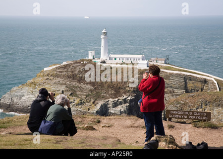 BIRDWATCHERS using binoculars to sea watch on cliffs with South Stack lighthouse on coast. Holyhead Holy Island - Stock Photo