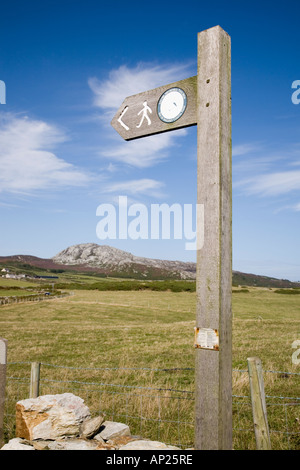 ISLE of ANGLESEY COASTAL PATH SIGN against blue sky with Holyhead Mountain (Mynydd Twr) in north Anglesey countryside - Stock Photo