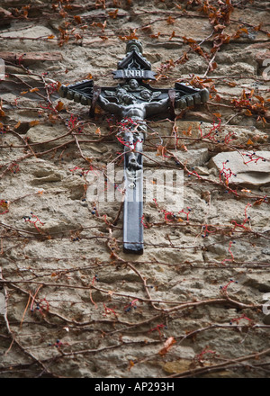 A black crucifix hanging on a wall in the Italian town of Triora, Northern Italy - Stock Photo