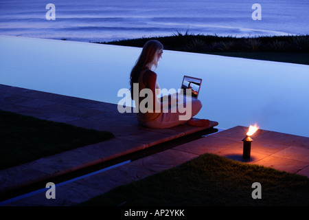 Young woman sitting with laptop at the edge of a swimming pool, looking at photographs, near Uluwatu, Bali, Indonesia - Stock Photo