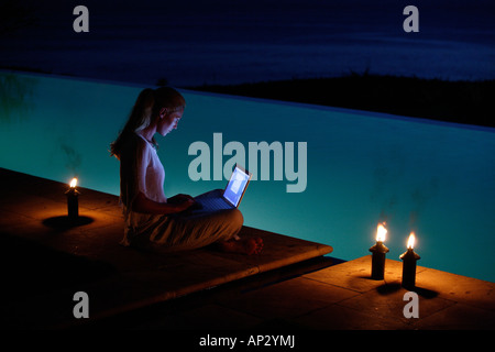 Young woman sitting with laptop at the edge of a swimming pool, near Uluwatu, Bali, Indonesia - Stock Photo