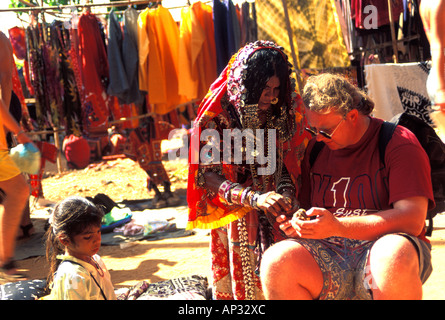 Karnatakan woman and western tourist at Anjuna Flea Market, Goa, South India - Stock Photo