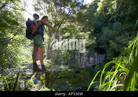 Mother and child on hanging bridge, rivercrossing in Abel Tasman National Park, north coast of South Island, New - Stock Photo