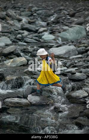 Girl crossing melting water, hiking at Franz Josef Glacier, Westland National Park, Westcoast, South Island, New - Stock Photo