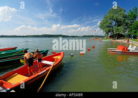 Two children fishing on rowing boat at beach of lake Simssee, Chiemgau, Upper Bavaria, Bavaria, Germany - Stock Photo