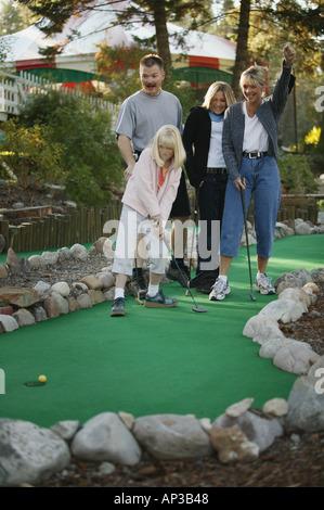 Family plays mini golf - Stock Photo